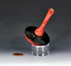 "Spin-top made from African Pink Ivory and Blackwood. Topping it off, a brass, copper and silver ""Mosaic Pin"" decorates the handle. With Rose Engine turnings, the top measures about 2.00"" wide at the base and stands about 3.25"" tall...by YoYoSpin.com"