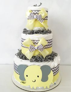 This adorable 3 Tier Elephant Diaper Cake is a colorful way to decorate the baby shower or a one-of-a-kind baby gift. The popular yellow and gray theme is a customer favorite. This Themed Diaper Cake would make the perfect centerpiece for the upcoming baby shower! Or to welcome home the sweet new bundle of joy! ELEPHANT CHEVRON DIAPER CAKE INCLUDES: ------------------------------------------------------------------------------------------------ 40-45 Pampers Swaddlers Disposable Diapers in…