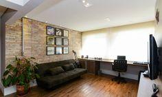 A parede clássica de tijolinhos nesse apartamento em São Paulo ganha destaque principalmente com a iluminação natural que entra por um janelão com persiana Henry Lopes / Divulgação
