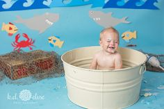 Happy smiling little boy taking a bath after his first birthday cake smash.