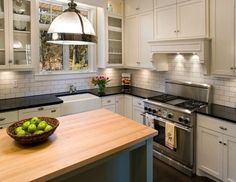 butcher block island with black counters and white subway tile