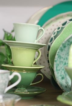 stacked green tea cups and saucers and green plates in the background