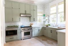 Gorgeous cottage kitchen boasts gray green shaker cabinets adorned with oil-rubbed bronze hardware paired with gray marble countertops and a white marble mini brick tile backsplash.