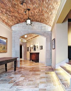 Limestone archways connect Turkish travertine floors and a vaulted brick ceiling in the curved basement hallway. Metal-and-alabaster ceiling pendants by ELK Group International and iron sconces by Paul Ferrante illuminate the space and the homeowners' art collection.