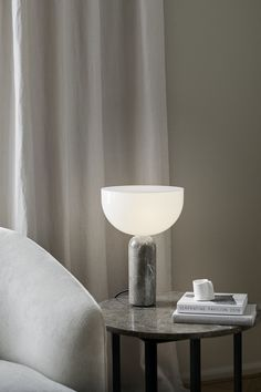 NEW WORKS KIZU TABLE LAMP Designed by Lars Tornøe for Danish design brand New Works, the Kizu lamp is a study of contrasts. The large head balances seemingly precariously on the slim marble body. Actually, the lamp is very sturdy. It's playful shape and sleek materiality has made it immediately popular with design-lovers around the world. The light itself is significant thanks to the large head, but not harsh.