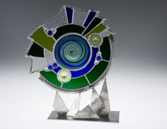 KATHLYN MILLER, ARTIST  - center blown rondel stained glass window in stainless steel stand  --