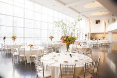 White wedding reception at Crocker Art Museum with bright citrus-colored floral arrangements. Flowers by Gingerleaf Floral. Photographer: Liz Caruana Weddings.