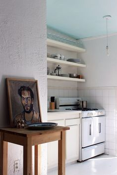 Marshall wanted to invest in antiques for the apartment, but he had a budget. That meant only minor changes—another coat of chalk-white paint and some inexpensive shelving—could be made in the kitchen | archdigest.com