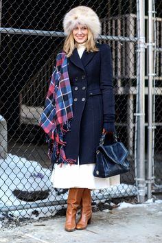 How to style a scarf - navy blue winter coat, worn with plaid blanket scarf draped over one shoulder, cream full midi dress, amazing fur hat + brown leather boots