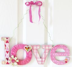 Valentine's Love Yarn Door Hanger craft made from a paper mache love sign decoupaged with Valentine's paper and wrapped in yarn.