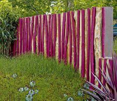 Sichtschutz aus Holzstämmen, unterschiedlich lackiert. Natur und trotzdem modern