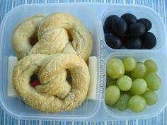 Homemade pretzels, Babybel cheese, Cheddar cheese sticks, Mozzarella cheese sticks, black olives, and green grapes
