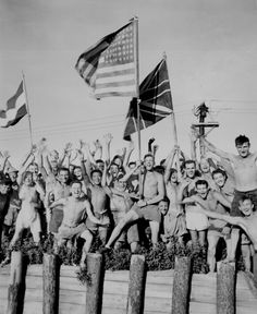 """Gaunt allied prisoners of war at Aomori camp near Yokohama cheer rescuers from U.S. Navy. Waving flags of the United States, Great Britain and Holland."" Japan, August 29, 1945. 80-G-490444."