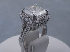 This is our splendid 6.82 ctw Cushion Cut Diamond Engagement Ring. It has a dazzling 6.01 ct G/SI3, Clarity Enhanced (Fracture Filled and Laser Drilled) Cushion Cut Center Diamond. Set in a beautifully designed 18k white gold setting, this ring is listed for $19,990.