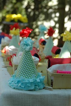 an adorable little table spread with favors and crafted party hats, perfect for a toddler's birthday