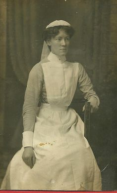 A fairly somber faced young Edwardian era nurse posing for a studio portrait. I like the tools (scissors, etc) tucked in her waistband - very clever.
