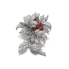 Ruby and diamond brooch, Van Cleef & Arpels Designed as a flower, the petals, stem and leaves set with circular-, single-cut and baguette diamonds, the pistils set with oval rubies, signed Van Cleef & Arpels, numbered, French assay and maker's marks, two small diamonds deficient.