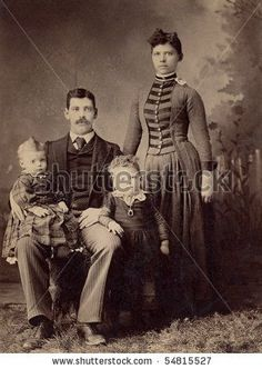 A 1800's antique vintage portrait photograph of a family posing for the camera.