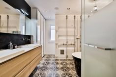 A modern white, black, and birch wood bathroom with stunning tiles and a unique recycled container door painted in white. One of a kind.