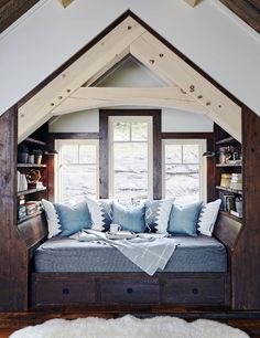 Super cozy and cute reading nook made out of dark wood, next to three windows