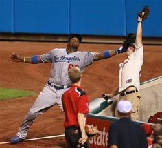 A fan gloves a foul ball by St. Louis Cardinals' Matt Adams, denying Los Angeles right fielder Yasiel Puig, left, an opportunity in the fourth inning of a baseball game Wednesday, Aug. 7, 2013, in St. Louis. (AP Photo/St. Louis Post-Dispatch, Chris Lee) EDWARDSVILLE OUT ALTON OUT