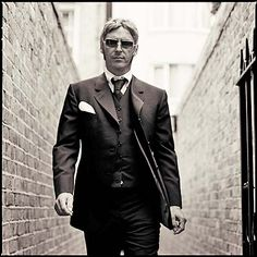 A black and white photo of a man in a suit walking down a brick alleyway