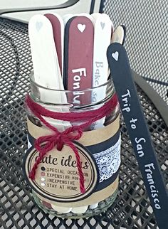 Date night idea diy mason jar.  Black = special occasion; red = expensive; tan = inexpensive; white = stay at home.  Made with a mason jar, parchment paper, black construction paper, lace ribbon, red string, jumbo popsicle sticks and acyrlic paint.