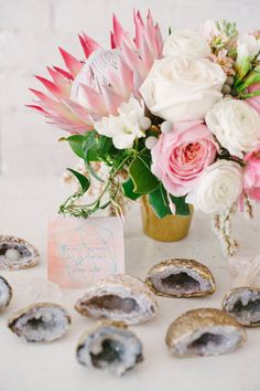 Bright pink and white flower arrangement and geode wedding favors.