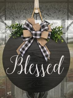 """Priority Mail Shipping is included at no additional charge! Door Hanger, Blessed Sign, Front Door Decor, Wood Door Sign, Front Door Sign, Year Round Wreath, Wreath, Door DecorBlessed Sign: 18"""" round door hanger; 1"""" thick. Made from real wood (not MDF), painted on both sides (black) and sealed. Blessed is in white. Greenery and bow can be changed out for different seasons. The rope hanger is approximately 6"""" long. Looking for a different color, size or saying, send me a message!Perfect for… Wooden Door Signs, Wooden Door Hangers, Wooden Doors, Custom Door Hangers, Welcome Signs Front Door, Front Door Decor, Front Doors, Door Reefs, Porches"""