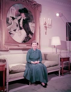 First Lady Mamie Eisenhower, circa 1954, wife of President Dwight D. Eisenhower, sits in front of a painted portrait of Edith Roosevelt, wife of Theodore Roosevelt, at the White House, Washington, D.C.