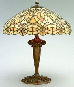 Duffner & Kimberly desk or table lamp having an Art Nouveau-style cast metal base, with mushroom shaped shade, amber, pale green and yellow stained glass.
