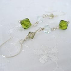 Graduating in size, these lovelies are Swarovski crystals in Jonquil Satin, Light Azore, & Olivine. Wire-wrapped in sterling silver, and finished with a hand-torched fine silver ball headpin, these crystals swing in harmony. Sterling silver ear wires. Measures 2 1/4 inches in length from top of ear wire to bottom of bead. These will be promptly made to order and quickly shipped.