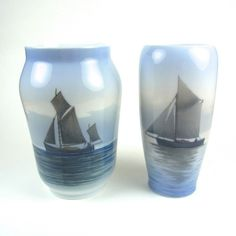 Two Royal Copenhagen sailing boat vases. Two Royal Copenhagen sailing boat vases. Both decorated with images of boats at sea, the larger vase, circa 1960, marked beneath with the green Royal Copenhagen Denmark stamp, three wavy lines in blue and numbered 2730/108, the more slender vase, circa 1894 - 1922, marked beneath with the green Royal Copenhagen stamp, three wavy lines in blue and numbered 2119/235. (2 items) 6.6 in (16.8 cm) height, 6.5 in (16.5 cm) height.