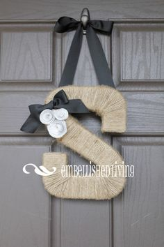 Monogram Wreath. Available on Etsy but an easy DIY! Monogram letter wrapped in twine with ribbon bow and paper rosettes accents.