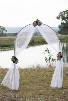Wedding arch covered with tulle and accented with flowers ceremony gorgeous ceremony arch decorated with tulle and king proteas weddings at peninsula wild flower junglespirit