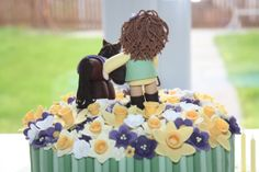 This is the 60th birthday cake I made for my friend's mum. A little horse and rider standing in a field of purple and yellow spring flowers with a few daffodills. This pic shows the back of the cake.