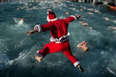 A competitor dressed in Christmas fancy jumps into the sea during the 105th Barcelona Traditional Christmas Swimming Cup at the Old Harbour of Barcelona on December 25, 2014 in Barcelona, Spain.