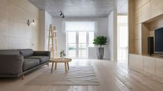 Wohnzimmer mit grauer Couch, Designer-Holzregal, runder Couchtisch aus Holz, eingebauter Fernsehregal