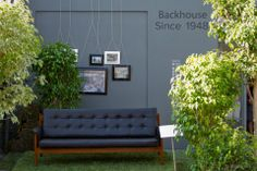 Outdoor living room Urbis Design Day 2013, gatherandhuntnz for Backhouse Ltd, Auckland  (outdoor-living-room, picture-frames, grey, grass, sofa, leafy, curation, exhibition-ideas, event-styling)