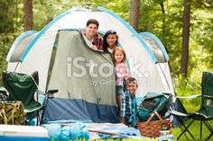 Family of four camping outdoors in forest. Tent, supplies. Royalty Free Stock Photo