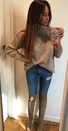 #spring #outfits woman wearing brown sweater and distressed blue denim bottoms standing near white wooden door. Pic by @the_haute_hunter