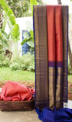 This iridescent pink kanchivaram silk has gold zari bhuttas all over. The border is in azure blue with intricately woven gold zari and a hint of orange and light green. The grand pallu in azure blu...