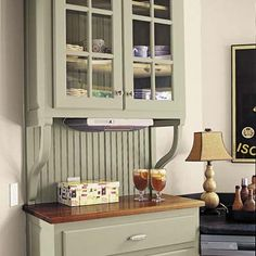 A glass-front hutch fitted with open brackets, a raised butcher-block surface, and a beadboard back adds vintage style to an oddly angled exterior wall. | Photo: Sara Essex | thisoldhouse.com