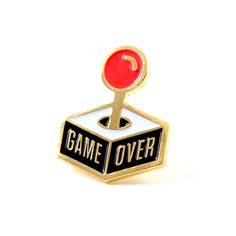 """Insert coin to continue - Gold pin with colored enamel - Rubber backing - Measures .5"""" tall x 1"""" wide"""