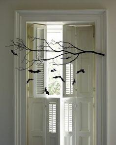 Spray paint a branch black then using contruction paper cut out bats & strig them up.