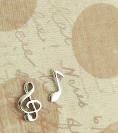 Dainty treble clef and music note stud earrings in solid sterling silver.