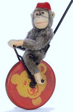 A STEIFF PUSH-A-LONG FLINKO, (322), brown mohair chimpanzee, brown and black glass eyes, pink felt face, ears, hands and feet, swivel head, jointed, red felt fez and FF button, seated on a wire and wood unicycle, the red wheel stenciled with a yellow Teddy Bear head, circa 1927 --27in