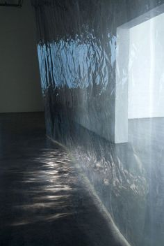 Wall of water installation by Anna Veronica Janssens. The sheerness and reflections cast by the light create a monochromatic range of colours and the illusion of movement. It almost looks like rippling water at night.