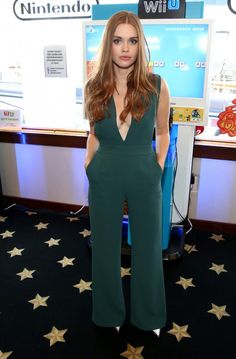 Holland Roden wears a teal jumpsuit with metallic pumps