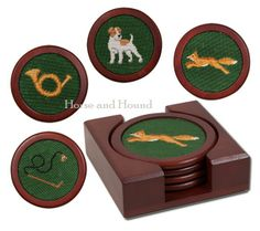 Foxhunt Coasters. Hand-stitched needlepoint art inlaid into polished circular wood base and finished with a cork back. The four coasters are presented in a handsome wood box. Four different images; Fox, Jack Russell Terrier, Hunting Whip and Hunting Horn create this handsome set of practical coasters.
